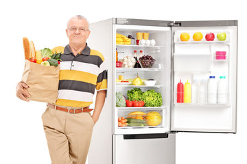 Mature man holding a grocery bag by a fridge