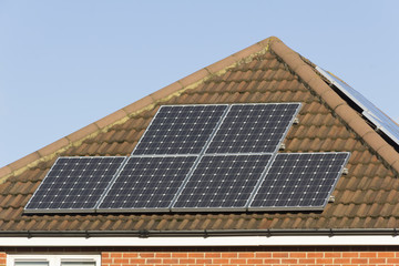 Solar panels for generating electricity on two aspects of the roof of a house in England.