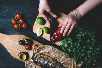 Hands in the process of cooking fish, pepper, parsley, tomato, lime on a black wooden background top view