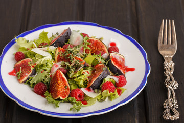 Salad with figs and raspberries, dressed with raspberry sauce and Parmesan cheese