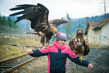 Girl photographed with an eagle. girl holds a large eagle on her hand. girl and  bird,  eagle and  girl,  girl and falcon