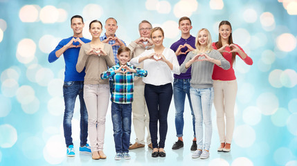group of smiling people showing heart hand sign