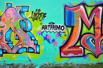 Colorful graffiti painted on a wall outside.
