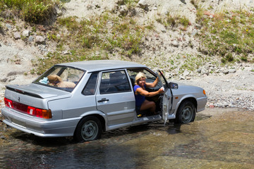 The woman washing a car outdoors
