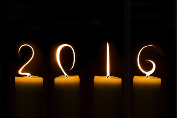 2016 written with candle flames on black background Fototapete