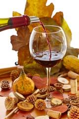 Glass of wine among autumn decoration