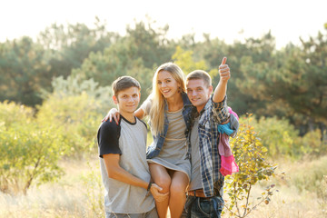 Guys holding a girl in the arms in the forest outdoors