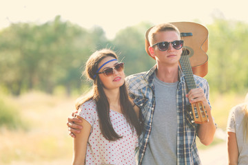 A young guy with guitar embraces a girl, outdoors