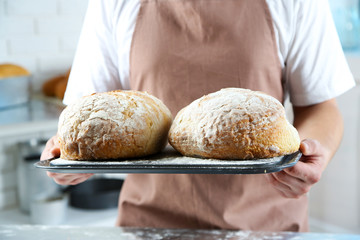 Baker checking freshly baked bread in kitchen of bakery