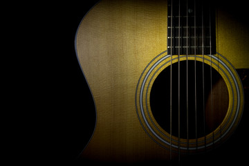 Acoustic guitar isolated on black background, horizontal view, low key image