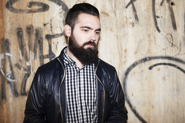 Attractive young man with beard, dressed in black leather jacket and black and white checkered shirt, looks to one side, behind has a wall with graffiti. Fashion. Hipster