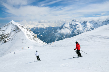 Two skiers skiing downhill on a sunny day, Austrian Alps