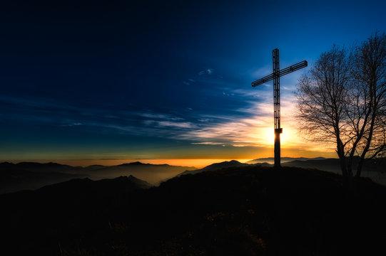 Summit cross a mountain at sunset