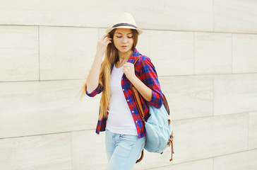 Pretty young girl wearing a summer straw hat and checkered shirt