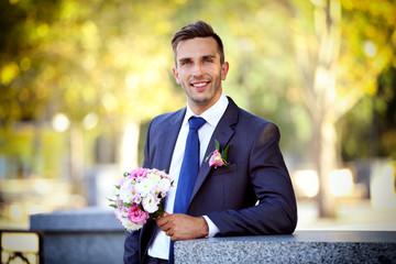 Groom holding wedding bouquet outdoors