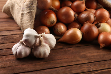 Scattered sac with fresh onions and garlic on wooden background