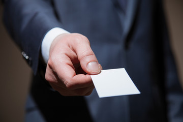 Man's hand reaching out a business card