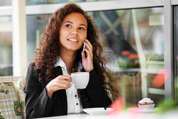 Young smiling woman speaking by cellphone and drinking coffee at the restaurant's terrace