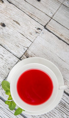 A cup of hibiscus tea and fresh mint leaves over wooden background
