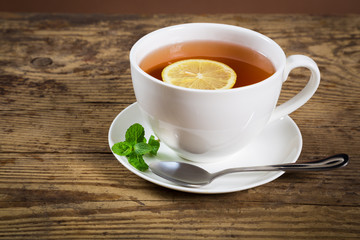 Cup of tea with mint leaf and lemon