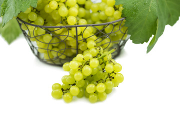Fresh green grapes on basket isolated on white.