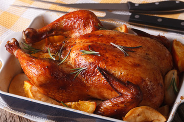 baked chicken with oranges and apples in the baking dish close-up.