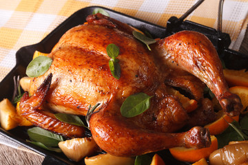 chicken roasted with oranges and apples closeup in a pan. horizontal