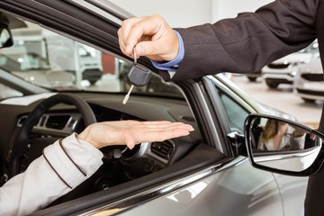 Salesman offering car key to a customers