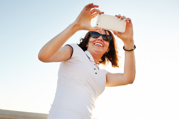 Girl in sunglasses is taking a selfie photo. Young woman making self picture with smartphone camera in summer day.
