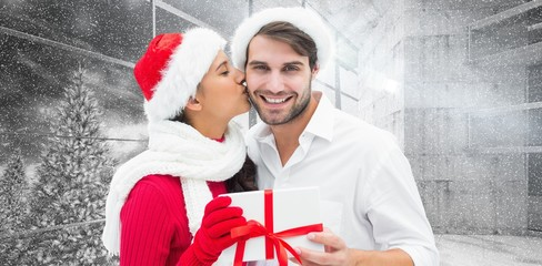 Composite image of festive young couple holding gift