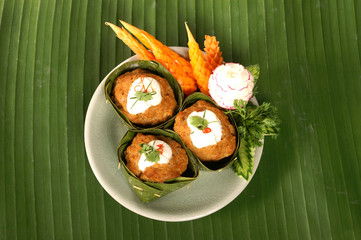 red curry mixed spicy herb with meat in banana leaf decoration by carving carrot and radish on banana leaf background