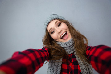 Laughing woman in hat and scarf making selfie photo