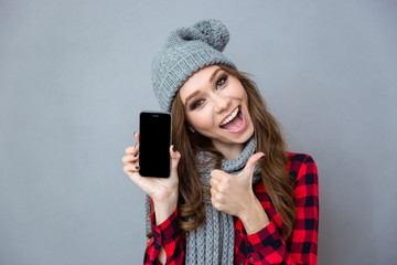 Woman showing blank smartphone screen and thumb up
