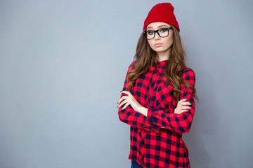 Serious hipster woman standing with arms folded