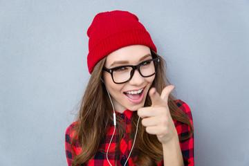 Cheerful woman pointing finger at camera