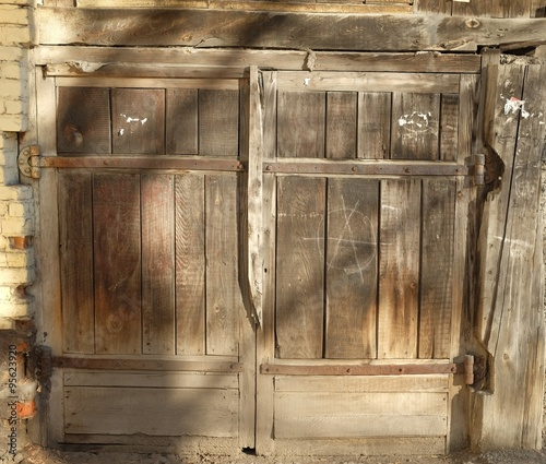 Old Wooden Garage Door With Shadows From The Branches Of The Tree