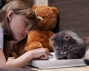 Кот и девочка читают вместе книгу. Ребенок водит пальцем по строчкам. Кот смотрит в книгу. Отношения ребенка с домашним животным, котом