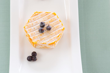 French cheese varieties camembert on a white plate in a box and without. dairy products. Free space for inscriptions.