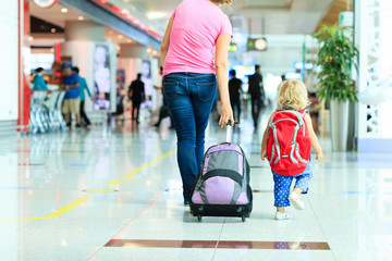 mother and little daughter walking in the airport