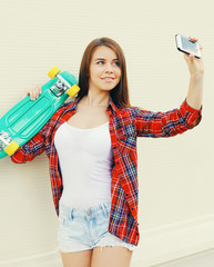Pretty cool girl with skateboard taking picture self portrait on