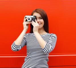 Pretty woman with retro vintage camera in city over red backgrou