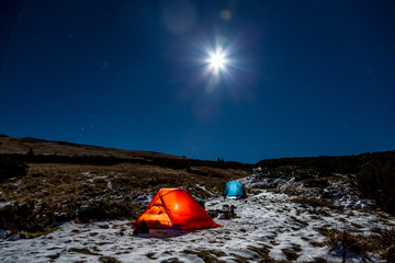 Winter Sport Hiking Bivouac in Mountain Landscape at Night with Bright Full Moon