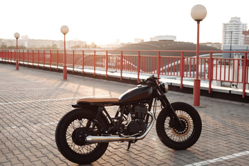 Vintage motorcycle in parking lot during sunset