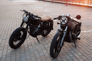 Two vintage motorcycle in parking lot during sunset