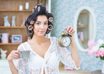 Morning rush. Beautiful woman in hair curlers holding cup of coffee in one hand and a clock in the other
