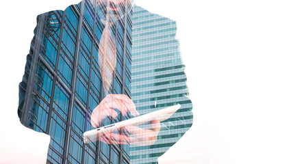 Double exposure of man with tablet and office building, white background