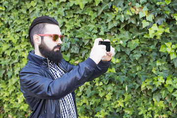 Modern and sexy man with beard make a picture with the Smartphone