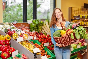Lächelnde Frau mit Gemüse im Supermarkt