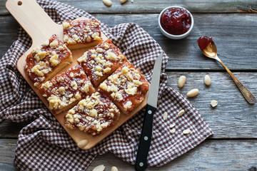 chopped shortbread with jam and cashew nuts on a board and a napkin