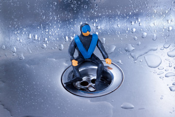 small plasticine diver sitting on a steel sink drain.metaphor.cleaning or repair of water supply system or sewerage